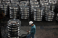 A worker stands among stacks of train carriage wheels at Ma Steel in Maanshan, China. With an additional plant that opened last year, Ma Steel is the world's largest producer of train carriage wheels with an annual capacity of 1.1 million units..29 Dec 2008.