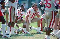 ROCKLIN, CA - Joe Montana of the San Francisco 49ers kneels on the sidelines during practice at training camp at Sierra College in Rocklin, California in 1988. Photo by Brad Mangin