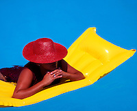 Woman wearing a red hat floating on a yellow inflatable raft in a swimming pool.