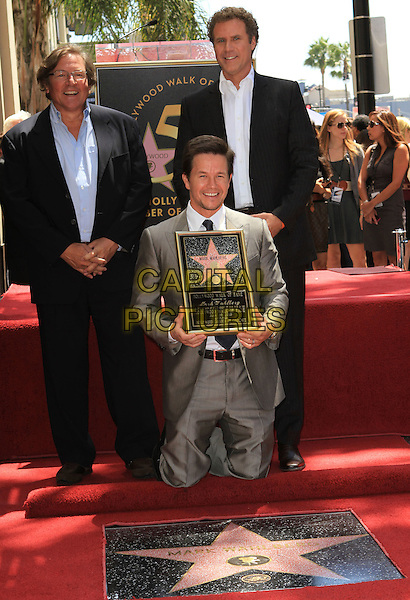 LORENZO DI BONAVENTURA, MARK WAHLBERG & WILL FERRELL.Mark Wahlberg is honored on The Hollywood Walk of Fame with the 2414th Star, Hollywood, CA, USA, .29th July 2010..full half  length grey gray suit tie shirt holding frame kneeling  black .CAP/ADM/FS.©Faye Sadou/AdMedia/Capital Pictures.