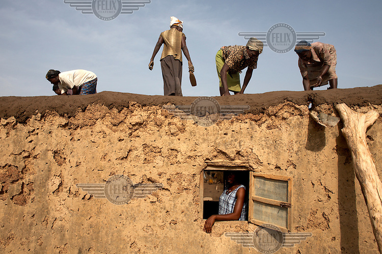 Women work on a new roof for a house near. The roof is made from mud which is compressed by beating it with a special wooden tool. The heavy rains mean repairs are regularly needed to the homes in northern Ghana, which are mostly built from just mud and sticks.