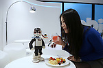 """A woman looks at a communication robot called """"Robi"""" as she holds """"Robi sonic"""", a cocktail drink inspired by the robot during a press preview for """"Robi cafe"""" where visitors can interact with the robots while enjoying meals and drinks in Tokyo, Thursday, January 15, 2015. The robot can be built by assembling parts sent along with a weekly magazine by Deagostini. The cafe will open from January 16 until February 8. (Photo by Yuriko Nakao/AFLO)"""