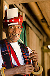 Older man in ceremonial dress lights up a traditional cigarette, Luba Village, near Bajawa, Flores, East Nusa Tenggara, Indonesia