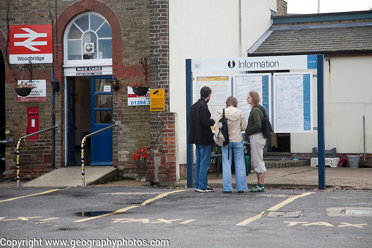 People looking at train timetable information at railway station, Woodbridge, Suffolk, England, Uk