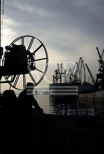 Varna, Bulgaria. Ships docked with dockside cranes; a man and a double wheel in silhouette in the foreground.