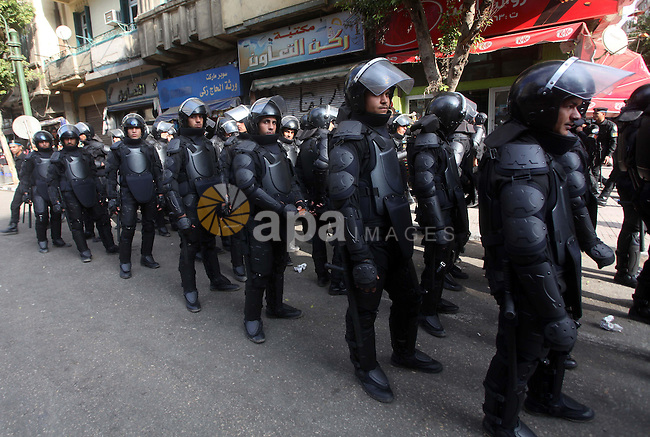 Egyptian riot police stand guard outside the Shura Council, the upper house of parliament where the Constituent Assembly drafted the country's new constitution, as protesters against Egypt's President Mohamed Morsi chant slogans in front of them, while Morsi gives a speech before a newly empowered senate in Cairo on December 29, 2012. Morsi said in the address, a disputed new constitution guaranteed equality for all Egyptians, and downplayed the country's economic woes. Photo by Ashraf Amra