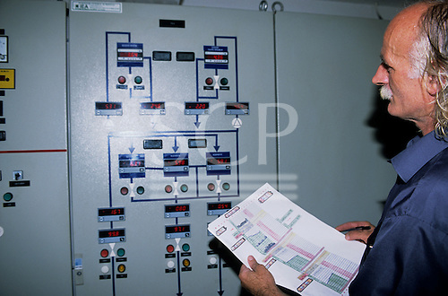 Brasov, Romania. Municipal water works; worker with digital controls.