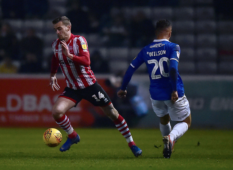 Lincoln City's Harry Toffolo under pressure from Exeter City's Kane Wilson<br /> <br /> Photographer Andrew Vaughan/CameraSport<br /> <br /> The EFL Sky Bet League Two - Lincoln City v Exeter City - Tuesday 26th February 2019 - Sincil Bank - Lincoln<br /> <br /> World Copyright © 2019 CameraSport. All rights reserved. 43 Linden Ave. Countesthorpe. Leicester. England. LE8 5PG - Tel: +44 (0) 116 277 4147 - admin@camerasport.com - www.camerasport.com