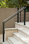 A sleek ,black metal railing contrasts the light grey stone steps.