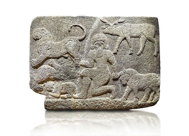 Picture & image of Hittite relief sculpted orthostat stone panel of Herald's Wall Basalt, Karkamıs, (Kargamıs), Carchemish (Karkemish), 900700 B.C. Anatolian Civilisations Museum, Ankara, Turkey.<br /> <br /> In the middle is a kneeling bearded figure holding the bull's horn with his left hand and the lion's hind leg with his right hand. Below this lion is another lion whose chest and the head are missing, and below this second lion is another small lion. A deer stands behind his head. It is thought that this relief depicts Gilgamesh, the master of animals. <br /> <br /> Against a white background.