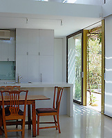 A concrete screed floor and laminated kitchen units have been used in this simple but modern open-plan kitchen/ dining area