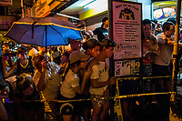 MANILA, PHILIPPINES - OCTOBER 06: Passers by watch as scene of the Crime Police investigators, SOCO, process a scene as surrenderee, Ryan Santillian, 29, lays dead in the middle of the street in the neighborhood of Makati on October 6, 2016 in Manila City, Philippines. Bystanders heard 6 gunshots around 9pm and found Mr Santillian dead in the street. The unknown gunman was on foot and shot the victim with a silencer according to eyewitnesses. Mr Santillian had surrendered himself in early July and was on the list of users that was in rehabilitation. Ryan left a wife and 2 children.  <br /> Photo by Daniel Berehulak for The New York Times