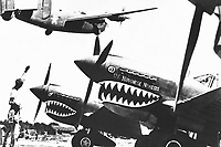 Landing wheels recede as this U.S. Army Air Forces Liberator bomber crosses the shark-nosed bows of U.S. P-40 fighter planes at an advanced U.S. base in China.  An American soldier waves good luck to the crew, off to bomb Japan.  Ca. 1943. Acme. (OWI)<br /> Exact Date Shot Unknown<br /> NARA FILE #:  208-N-15394<br /> WAR & CONFLICT BOOK #:  1150