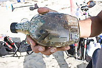"Saturday, June 21 2009.  Pacific Beach, San Diego, CA, USA:  Dr Marcus Eriksen of the environmental group Algalita Marine Research Foundation (AMRF) displays a sample of ""plastic soup"": marine debris that he recovered from the North Pacific Gyre last year.  Eriksen and his wife Anna Cummins were in PB one day after completing a six-week journey from Vancouver to TJ to raise awareness about marine debris.   The couple spoke at 40 different events along the way and presented 5 mayors with samples of the ""plastic soup"".  The confluence of currents in a remote part of the Pacific known as the North Pacific Gyre has created a high concentration of marine debris - particularly plastics - that is clogging the area, endangering marine life and entering our food chain.  A lantern fish is seen in the middle of the frame - this fish is known to eat a lot of the plastic debris and is in turn eaten by the larger fish that end up on our dinner tables."