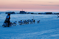 Aliy Zirkle runs on the trail past fish camps and tripod trail markers at sunset heading toward the finish at Nome on Wednesday March 14th during the 2018 Iditarod Sled Dog Race.  <br /> <br /> Photo by Jeff Schultz/SchultzPhoto.com  (C) 2018  ALL RIGHTS RESERVED