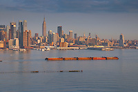 Long barge in Hudson river with manhattan skyline on background