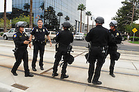 Phoenix, Arizona. April 25, 2012 - Phoenix Police officers standing on the Metro Light Rail northbound tracks on Central Avenue, assess the situation moments after a group of six protesters blocked traffic during rush hour. About 500 people protested the controversial law on the same day U.S. Supreme Court justices heard legal arguments on the Arizona vs. United States case. At the end of the march, six activists blocked Central Avenue by sitting in the middle of the street. They all were arrested by the Phoenix Police Department and taken to the Fourth Avenue County Jail. Photo by Eduardo Barraza © 2012