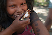 Aldeia Baú, Para State, Brazil. Kayapo girl eating a babassu nut, broken open to show the white inside.