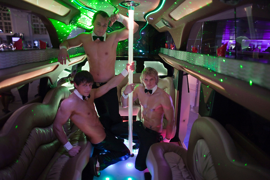 Moscow, Russia, 24/10/2009..Male strippers at the Millionaire Fair in Moscow inside a Hummer SUV converted into a stretch limousine with bars, dancing pole and high-end entertainment systems.The event has become an annual fixture, attracting thousands of would-be and existing Russian millionaires to view and purchase a wide range of luxury goods. This year however the fair was much smaller, an indication of how the formerly booming Russian economy has been hit by the world financial crisis.