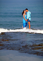 Young couple kissing in ocean surf.