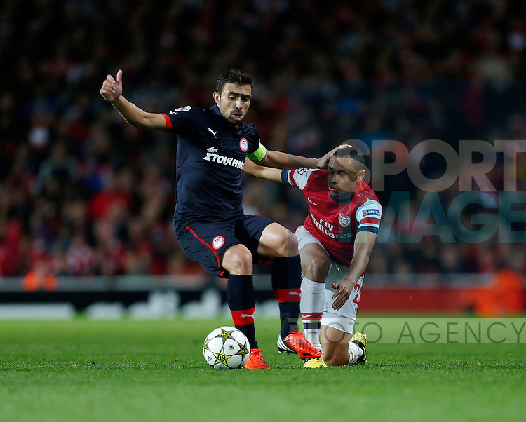 Arsenal's Francis Coquelin tussles with Olympiacos' Giannis Maniatis..Football - Champions League Matchday 2 - Emirates Stadium, London - 3/10/12 ..Mandatory Credit: David Klein/Sportimage..EDITORIAL USE ONLY. No use with unauthorized audio, video, data, fixture lists, club/league logos or ?live? services. Online in-match use limited to 45 images, no video emulation. No use in betting, games or single club/league/player publications. Please contact your account representative for further details....