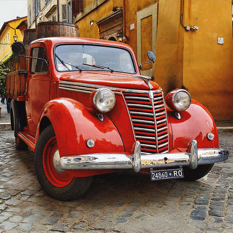 Retro transport of red delivery truck in European street
