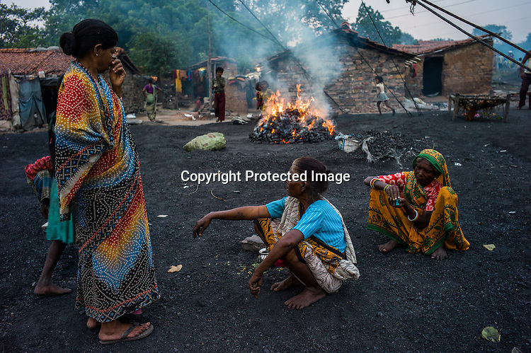Local villagers sit next to the coking coal in Bokapahari village in Jharia, outside of Dhanbad in Jharkhand, India.  Photo: Sanjit Das/Panos