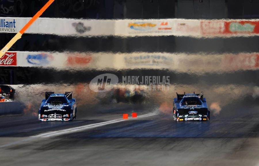 Nov 11, 2010; Pomona, CA, USA; NHRA funny car driver Matt Hagan (left) races alongside John Force during qualifying for the Auto Club Finals at Auto Club Raceway at Pomona. Mandatory Credit: Mark J. Rebilas-