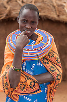 Young Masai woman in her traditional handcrafted beadwork and patterned orange cloth shawl in Kenya, Africa (photo by Travel Photographer Matt Considine)