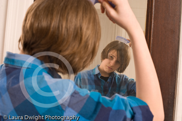 Teenage boy looking at self in mirror brushing combing or adjusting hair Caucasian horizontal age 14
