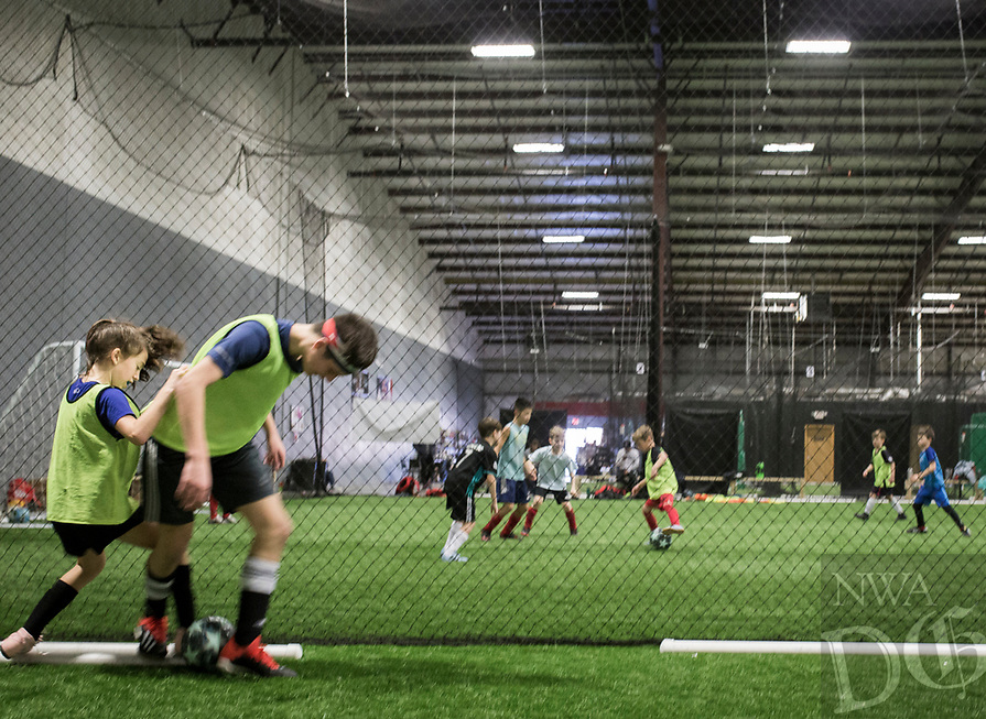 NWA Democrat-Gazette/CHARLIE KAIJO Reagan Crusinbery, 10, of Centerton and Davis Infante, 13, of Centerton (from left) play one-versus-one during a three-day New Year's Soccer Camp, January 4, 2019 at Strike Zone Training Academy in Rogers. <br />