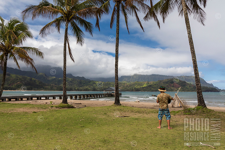 A man plays a guitar on Hanalei Beach near Hanalei Pier, Kaua'i.