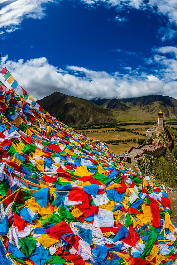 Thousands of prayer flags drape a mountain above the Yambulakhang Palace, Tibet, China. The five colors of the prayer flags represent the five elements: blue for sky, white for wind, red for fire, green for water, and yellow for earth.