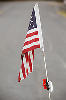 Morehead City, NC -- An American flag and flashers. Quadriplegic hand cyclist Paul Kelly, 62, trains for the Boston Marathon Tuesday, March 27, 2018. (Justin Cook for The Wall Street Journal)<br /> <br /> SUMMARY:<br /> <br /> Paul Kelly, hand cyclist, Beaufort, NC Training for the Boston Marathon so we would want to shoot in March to run the week before the marathon or marathon Monday, Apriln16. Life as a quadriplegic doesn&rsquo;t keep 62-year-old Paul Kelly on the sidelines. After breaking his neck in a swimming accident in 1978, Kelly was determined to find fitness activities to maintain an active lifestyle. He discovered handcycles while watching his niece compete in the 2006 Marine Corps Marathon and was inspired to start his own marathon career to stay fit. Paul has competed in over 100 half and full marathons. On April 16, he will celebrate his 40th year of living as a quadriplegic by taking on one of the most coveted races for a marathoner -- the Boston Marathon. Kelly is among the 60 handcyclists competing in the 2018 Boston Marathon with a qualifying time of 1:26:37. Most of Paul&rsquo;s distance training takes place at Bogue Banks, which includes Atlantic Beach, Salter Path, and Emerald Isle, N.C. It&rsquo;s Nicholas Sparks worthy scenery with its marshes, waterways, inlets and small islands. Paul is particularly fond of the approach from Atlantic Beach to Bogue Banks -- it&rsquo;s via the high-rise bridge. In cold weather, Paul has to be mindful of the environment and dress in a manner that insulates his legs while also allowing his upper body to ventilate. Paul chooses to train at times of day when the temperatures are more reasonable. He uses hand warmers in his gloves, on the inside the grips on his handcycle and in the legs of his trousers.