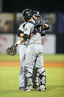 Pulaski Yankees relief pitcher Miles Chambers (56) gets a hug from catcher Victor Rey (14) after closing out the win over the Danville Braves at American Legion Post 325 Field on August 1, 2016 in Danville, Virginia.  The Yankees defeated the Braves 4-1.  (Brian Westerholt/Four Seam Images)