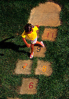 Young African-American girl playing hopscotch.