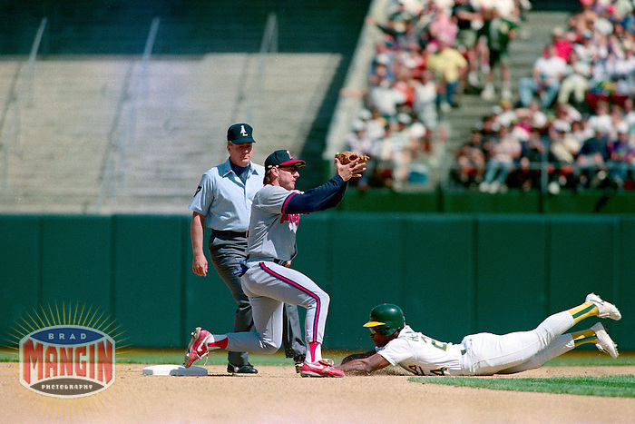 OAKLAND, CA - Rickey Henderson of the Oakland Athletics steals second base during a game against the California Angels at the Oakland Coliseum in Oakland, California in 1990. Photo by Brad Mangin
