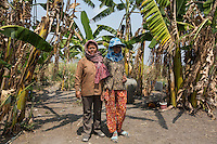 "Cambodia - Kampong Speu Province - Chheuon Khorn, 40, and her daughter Lak Chantrea, 15, from Trapang Khorn standing in the garden of their house. After their land was taken in 2010, the pair moved to Pis, in order to work as labourers inside the sugar plantation. ""The work is very hard and the pay is low. We work for ten hours a day and get 3,5 USD. It's like forced labour"", complains Chheuon. In exchange for her two hectares of land, Chheuon got a piece of land of 40x50 metres for her house, plus a compensation of 125 USD. Her daughter Lak, who would like to become a teacher, works in the plantation as well."
