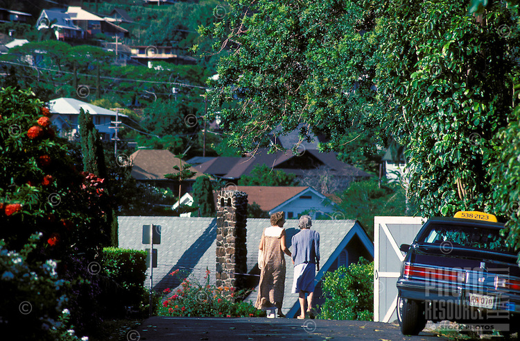 A close up view of beautiful Manoa valley with people walking along the street