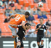 Washington D.C. - May 17, 2014:  David Horst (18) of Houston Dynamo heads the ball against Fabian Espindola (9) of D.C. United. D.C. United defeated  the Houston Dynamo 2-0 during a Major League Soccer match for the 2014 season at RFK Stadium.