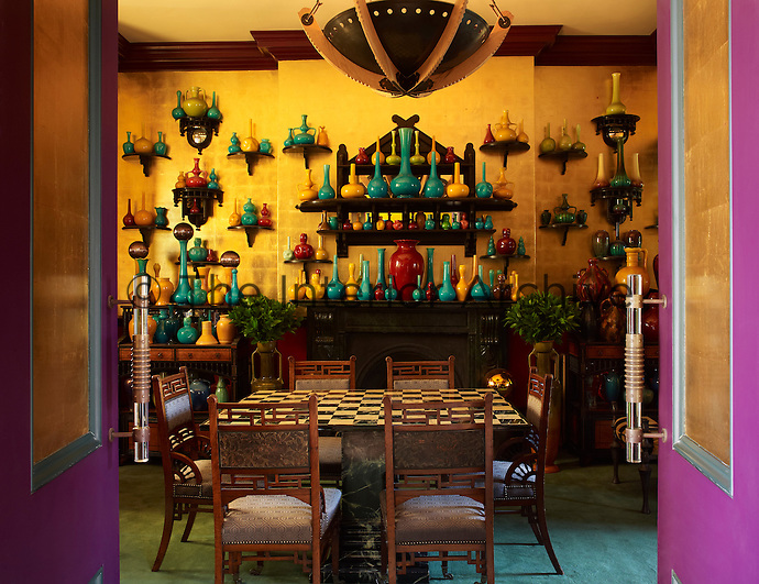 Collett's collection of 19th century studio pottery is displayed against a wall of gold leaf in the dining room