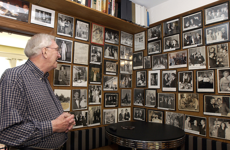 Sid Yudain looks at some of his Roll Call photos in his home in Georgetown.