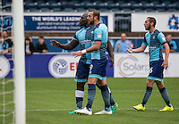 Adebayo Akinfenwa, Paul Hayes and Michael Harriman of Wycombe Wanderers try to calm the fans down after the Sky Bet League 2 match between Wycombe Wanderers and Colchester United at Adams Park, High Wycombe, England on 27 August 2016. Photo by Liam McAvoy.