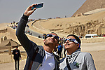 Egyptians take selfie during look up to view a partial solar eclipse around the Giza Pyramids, on the outskirts of Cairo, March 20, 2015. A partial eclipse was visible on Friday, the first day of northern spring, across parts of Africa, Europe and Asia. The total eclipse of the sun was only visible in the Faroe Islands and the Norwegian archipelago of Svalbard in the Arctic Ocean. Photo by Amr Sayed