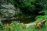 Wooden bench for two overlooking grindstone creek and the facing bluffs in summer