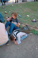Saint Petersburg, Russia, August 2002..Young fans of Russian pop singer Zemfira drink and & play her songs on a battered  - and borrowed - guitar on Nevsky Prospect.....