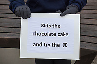 """Denise Gieseke, of Lincoln, Mass., holds a sign reading """"Skip the chocolate cake and try the [pi symbol]"""" at the March for Science demonstration in Harvard University's Science Center Plaza in Cambridge, Massachusetts, on Sat., April 22, 2017. On the other side of her sign, a message read, """"""""Alt Facts = [square root of negative one]."""" The square root of negative one is i, an imaginary number."""