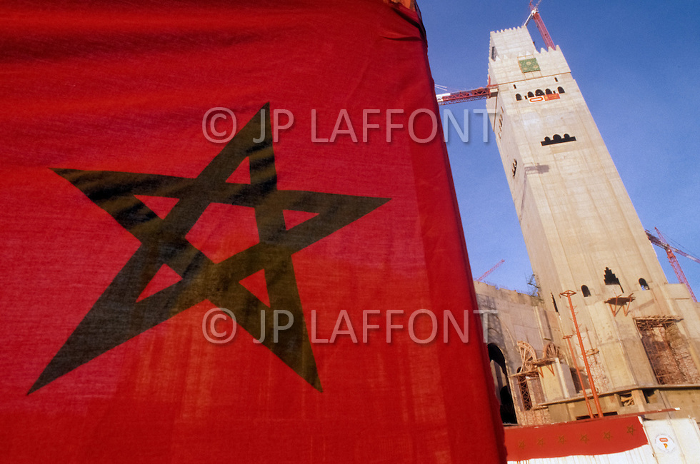 March 5, 1989, Casablanca, Morocco. Moroccan flag in front of the construction of the Hassan II Mosque,in Casablanca, built by the French industrial group Bouygues, founded by Francis Bouygues, and conceived by French architect Michel Pinseau.