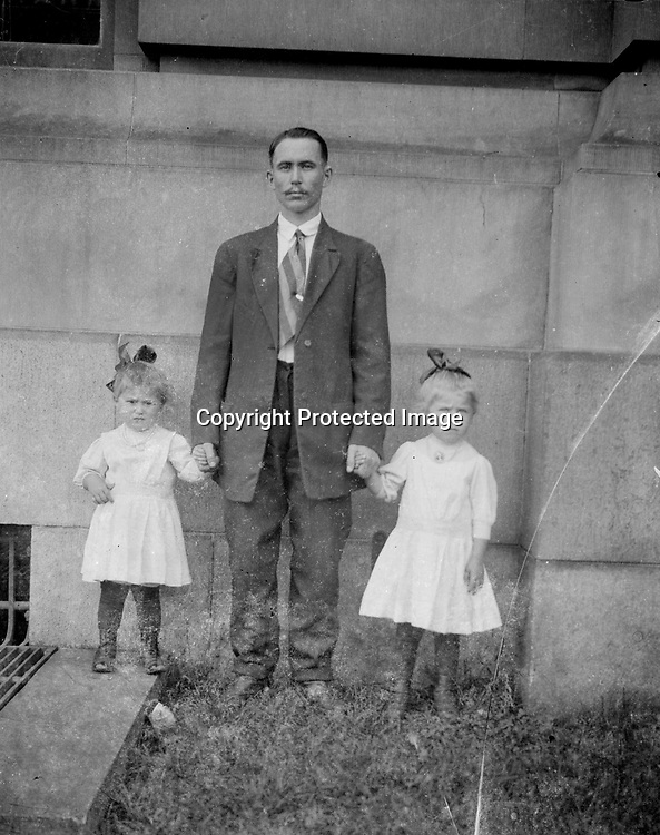 FATHER AND DAUGHTERS. This father and his fair-haired daughters stand beside the massive stonework of the Lincoln post office and courthouse. Perhaps he was a coworker of John Johnson in that building.<br /> <br /> Photographs taken on black and white glass negatives by African American photographer(s) John Johnson and Earl McWilliams from 1910 to 1925 in Lincoln, Nebraska. Douglas Keister has 280 5x7 glass negatives taken by these photographers. Larger scans available on request.