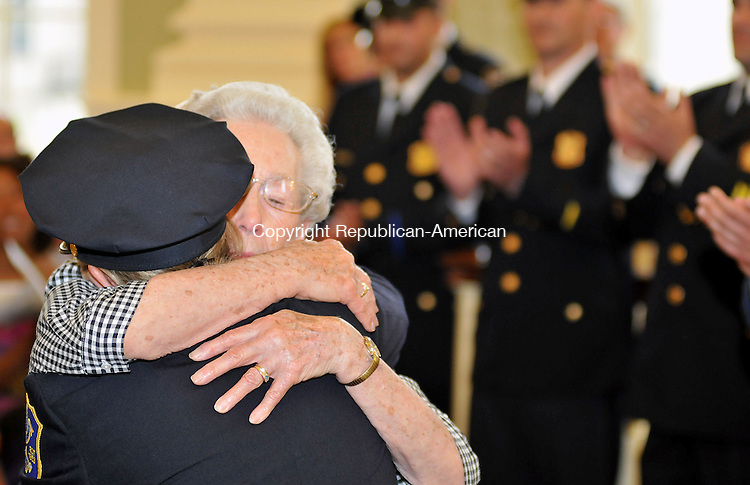 WATERBURY, CT, 21 JUNE 2011-062111JS11--Waterbury Police Decetive Cathleen Knapp gets a hug from her grandmother Alica Casazza after receiving her new badge during the Waterbury Police Department promotion ceremony Tuesday in the Aldermanic Chambers at Waterbury City Hall on Tuesday. A total of nine officers were promoted. <br /> Jim Shannon/Republican-American